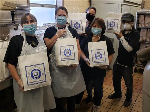 Alameda Unified school nutrition staff holding census 2020 bags with student meals